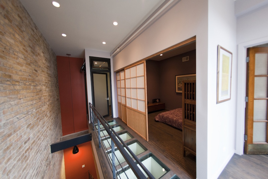 An image of a glass panel walkway in a loft renovation. On the right is a shoji screen door leading to a bedroom.