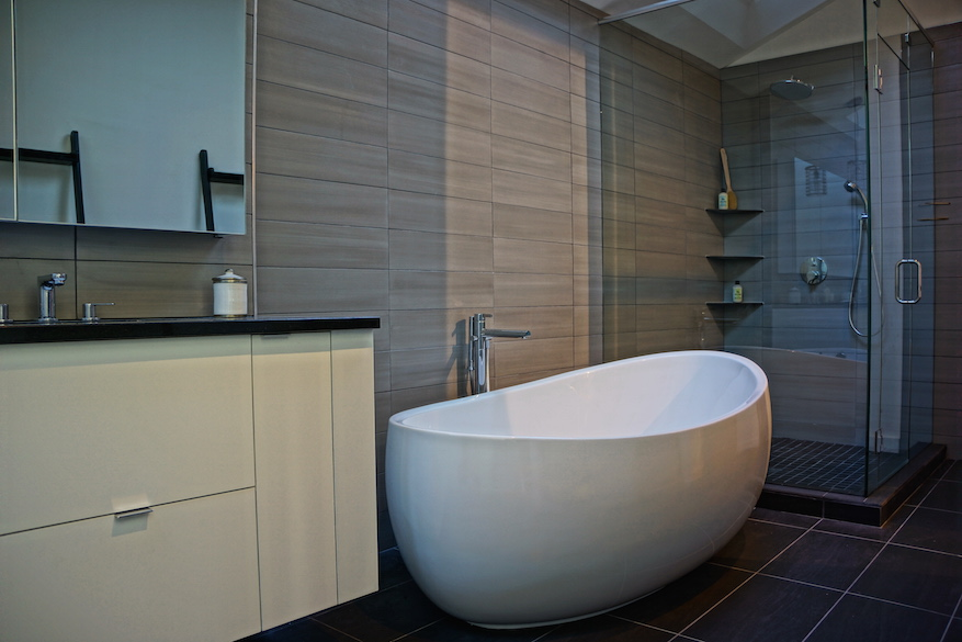 Image of a modern bathroom renovation with a free standing tub and glass walk-in shower.