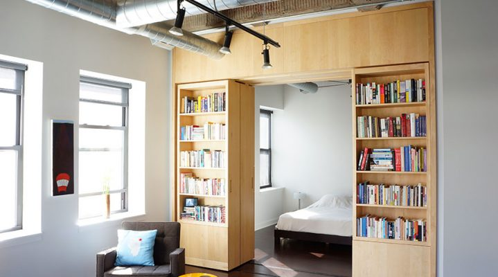 Picture of a modular bookcases on a track slid apart so you can see a bedroom behind them