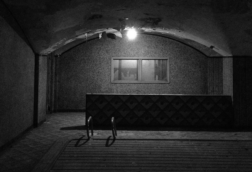 Before shot of the Lawrence House hotel pool covered with vintage tile and an arcing ceiling. It is black and white.