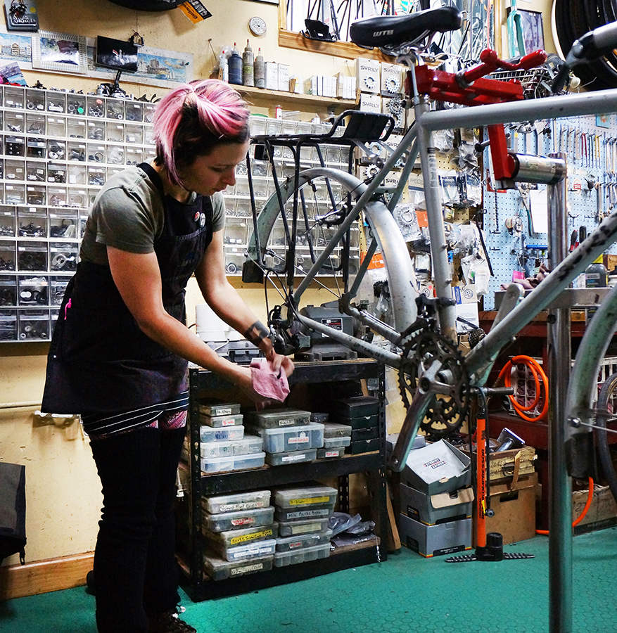 Picture of a girl repairing a bike in Logan Square